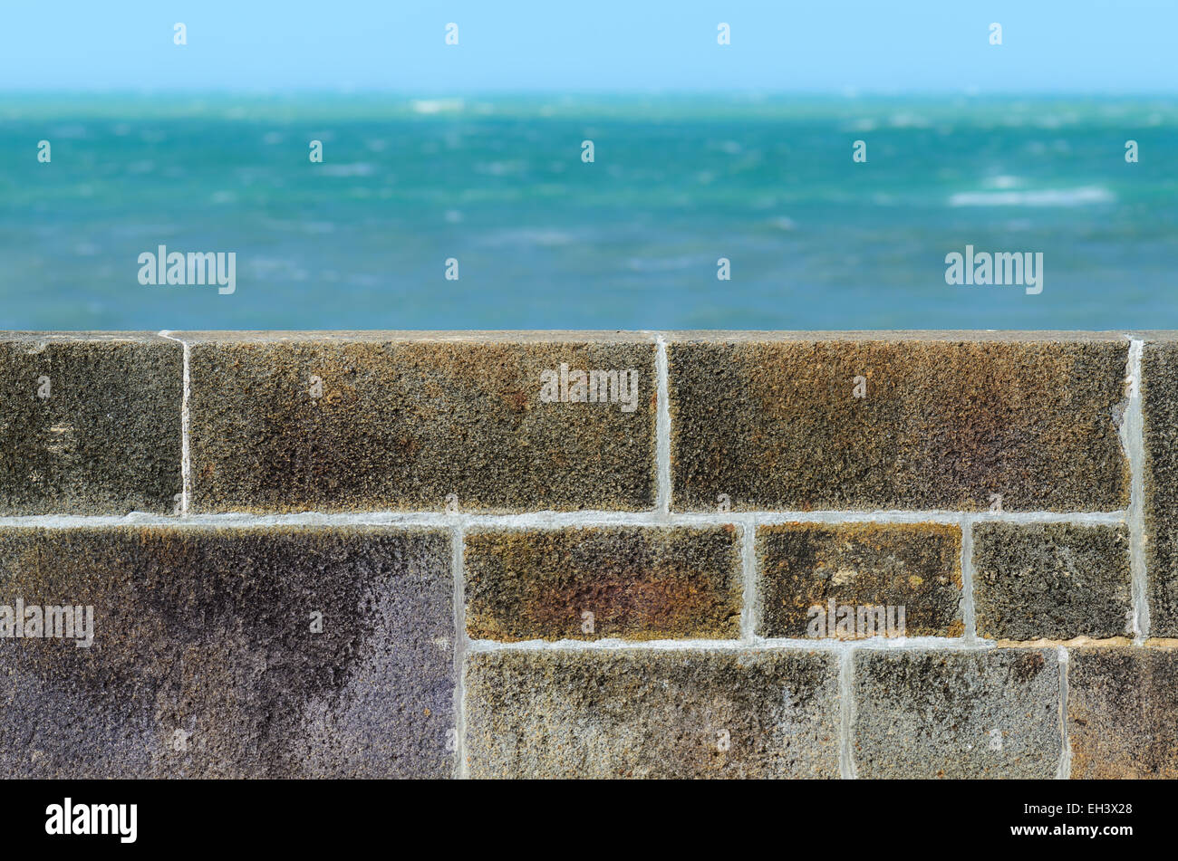 Stone fence wall and greenish turquoise sea in the distance Stock Photo