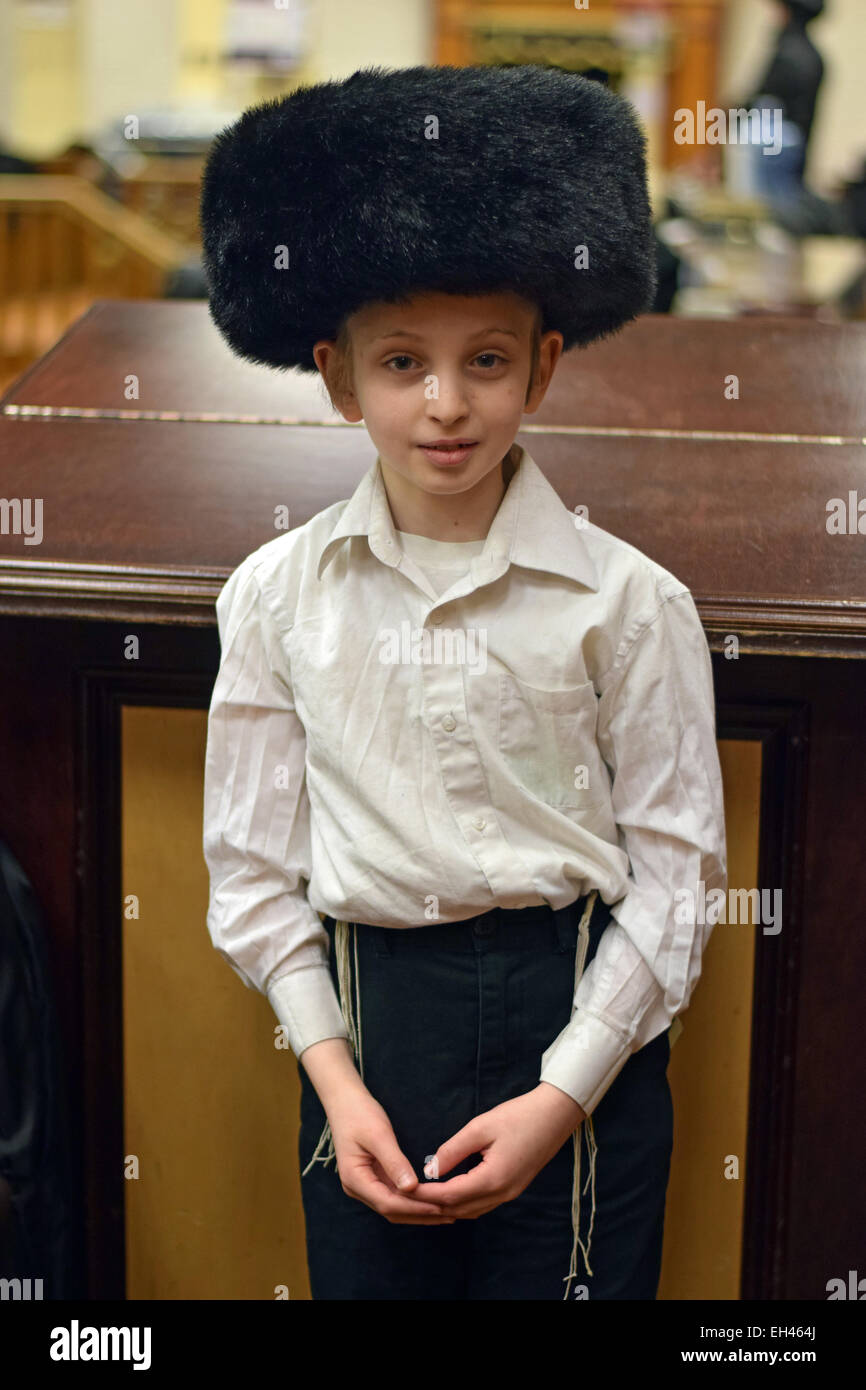 An young religious Jewish boy in a Purim costume in a synagogue in Crown Heights, Brooklyn, New York - Stock Image