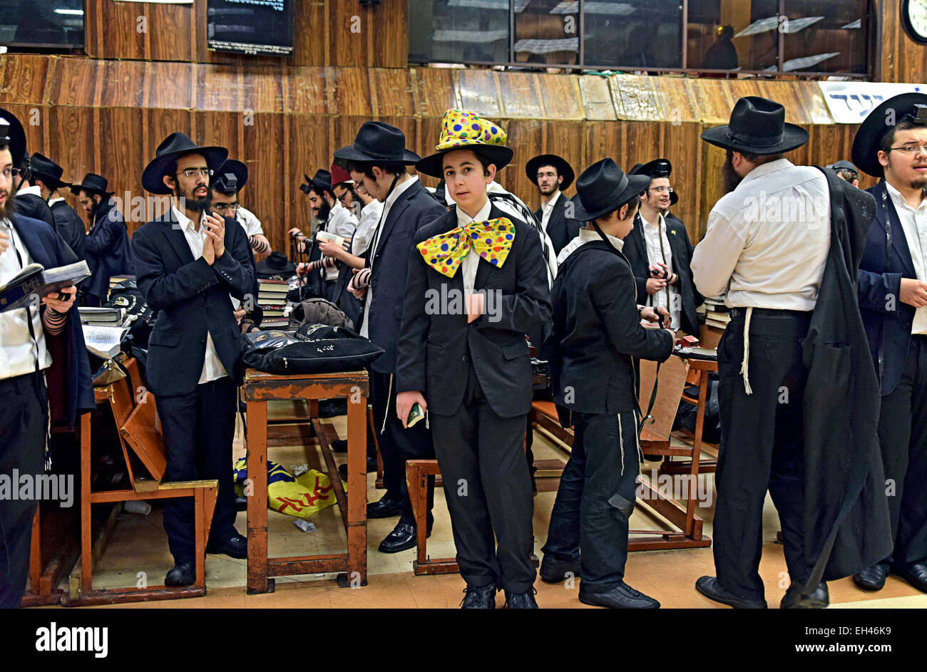 A group of religious Jewish men including including one in a Purim costume at a synagogue in Brooklyn, New York. - Stock Image
