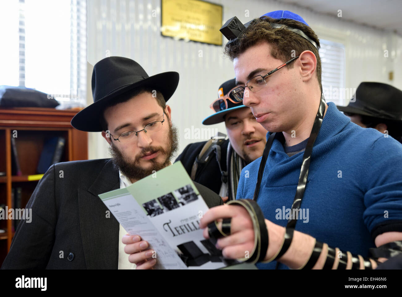 A religious Jewish man praying with 2 non-religious boys at a Shabbaton at the Ohel in Cambria Heights, Queens, - Stock Image