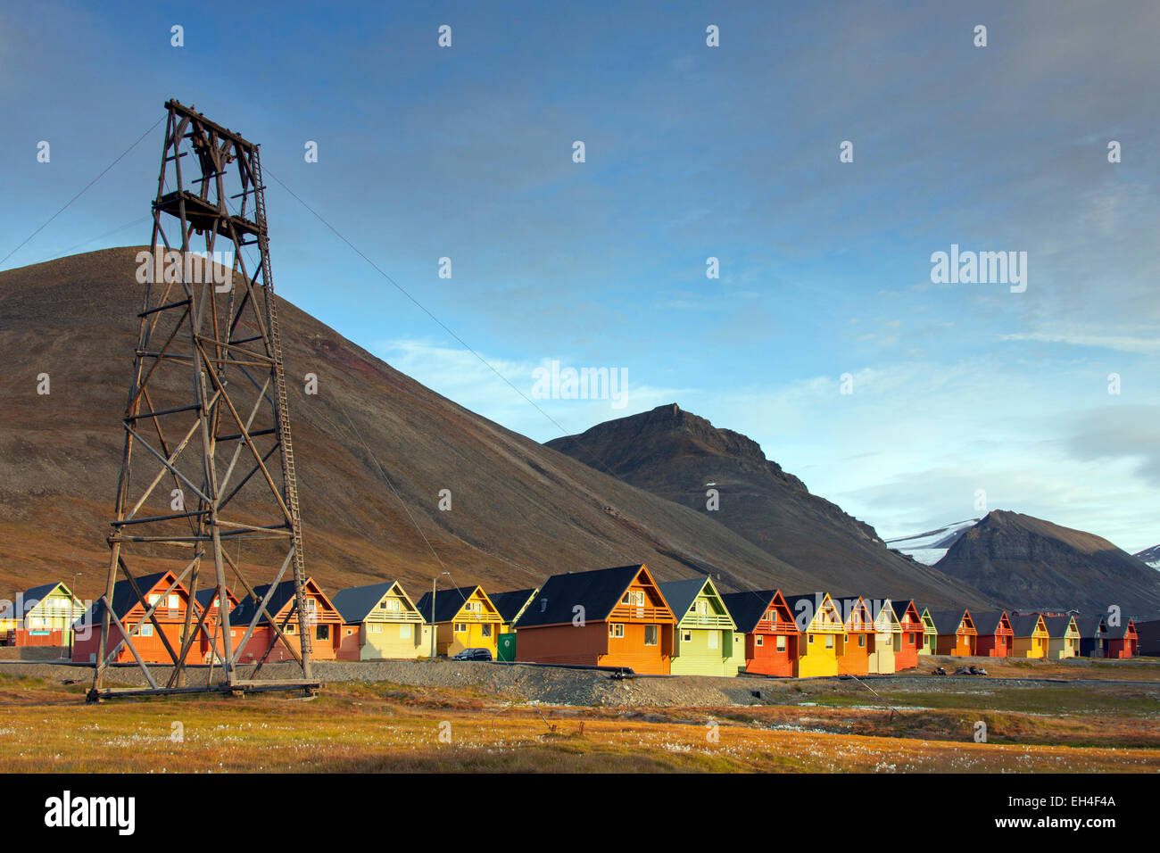 Cableway from abandoned coal mine and colourful wooden houses in the settlement Longyearbyen in summer, Svalbard, - Stock Image
