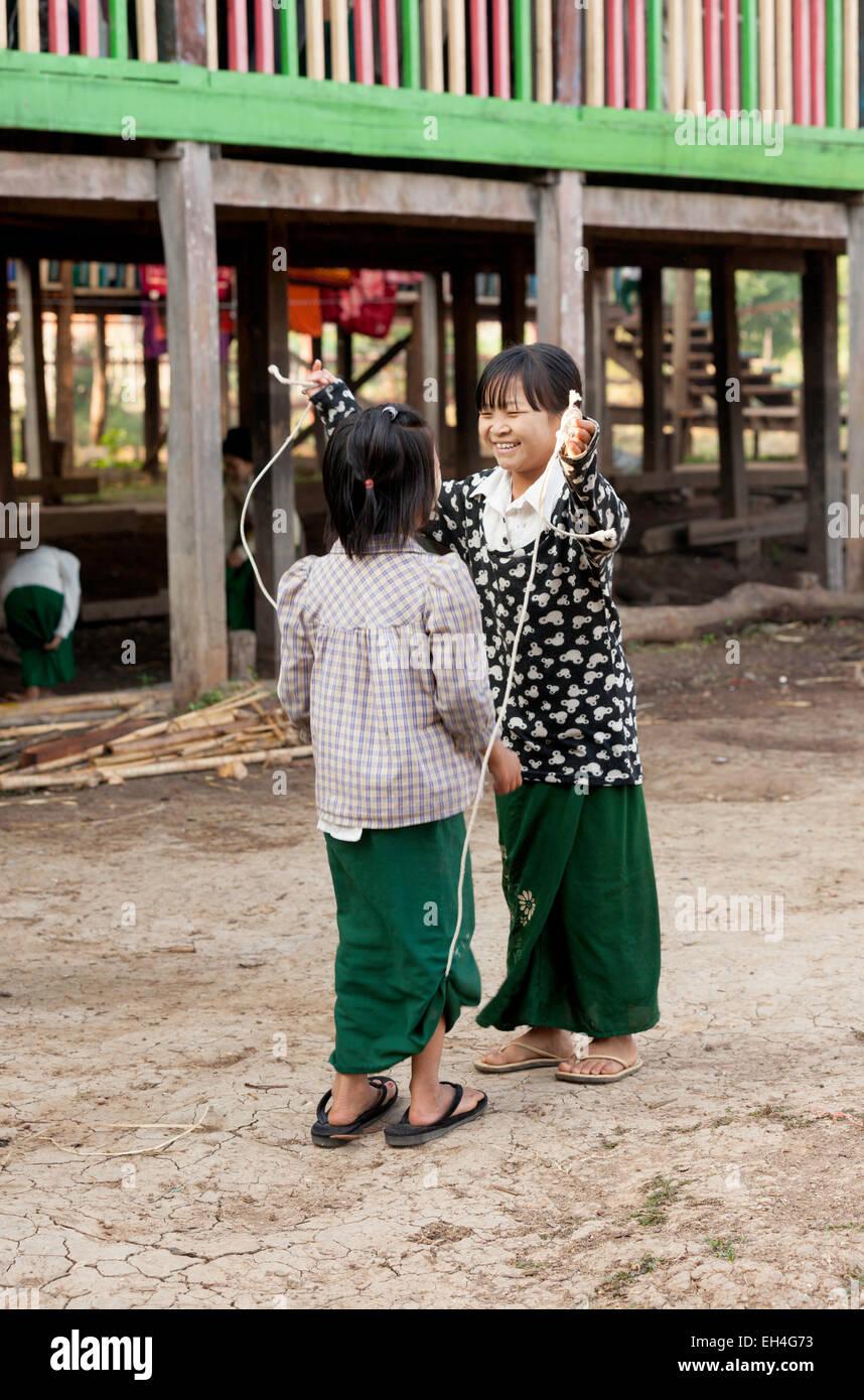 Two young children skipping in their school yard, Inle Lake, Myanmar ( Burma ), Asia - Stock Image