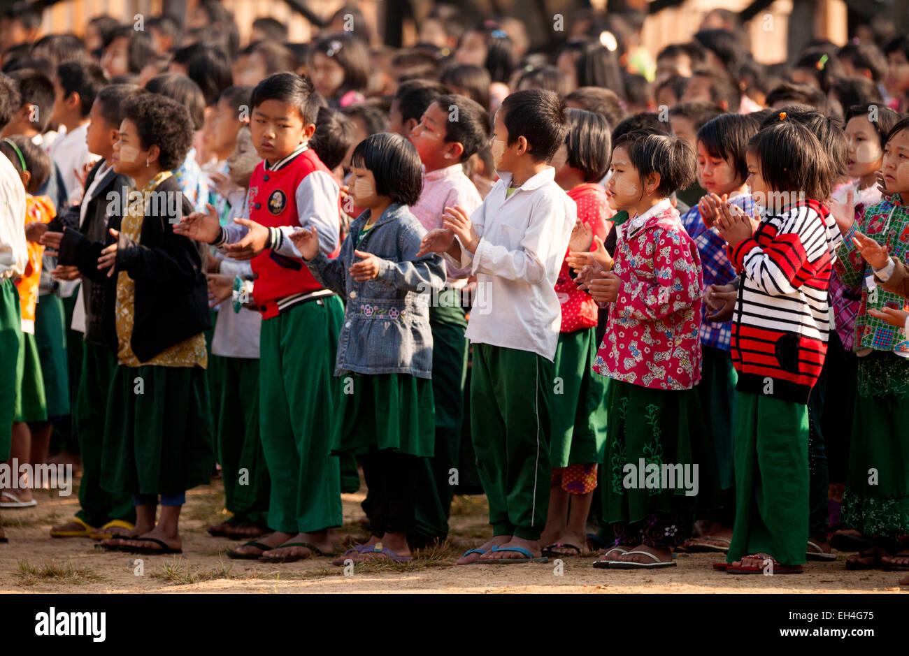 Burmese schoolchildren waiting in line at assembly in their school, Kay Lar village school, Inle Lake, Myanmar ( - Stock Image