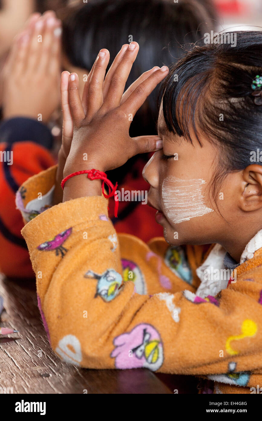 Child praying at the beginning of the days classes in her school, Kay Lar village, Inle Lake, Myanmar ( Burma ), - Stock Image