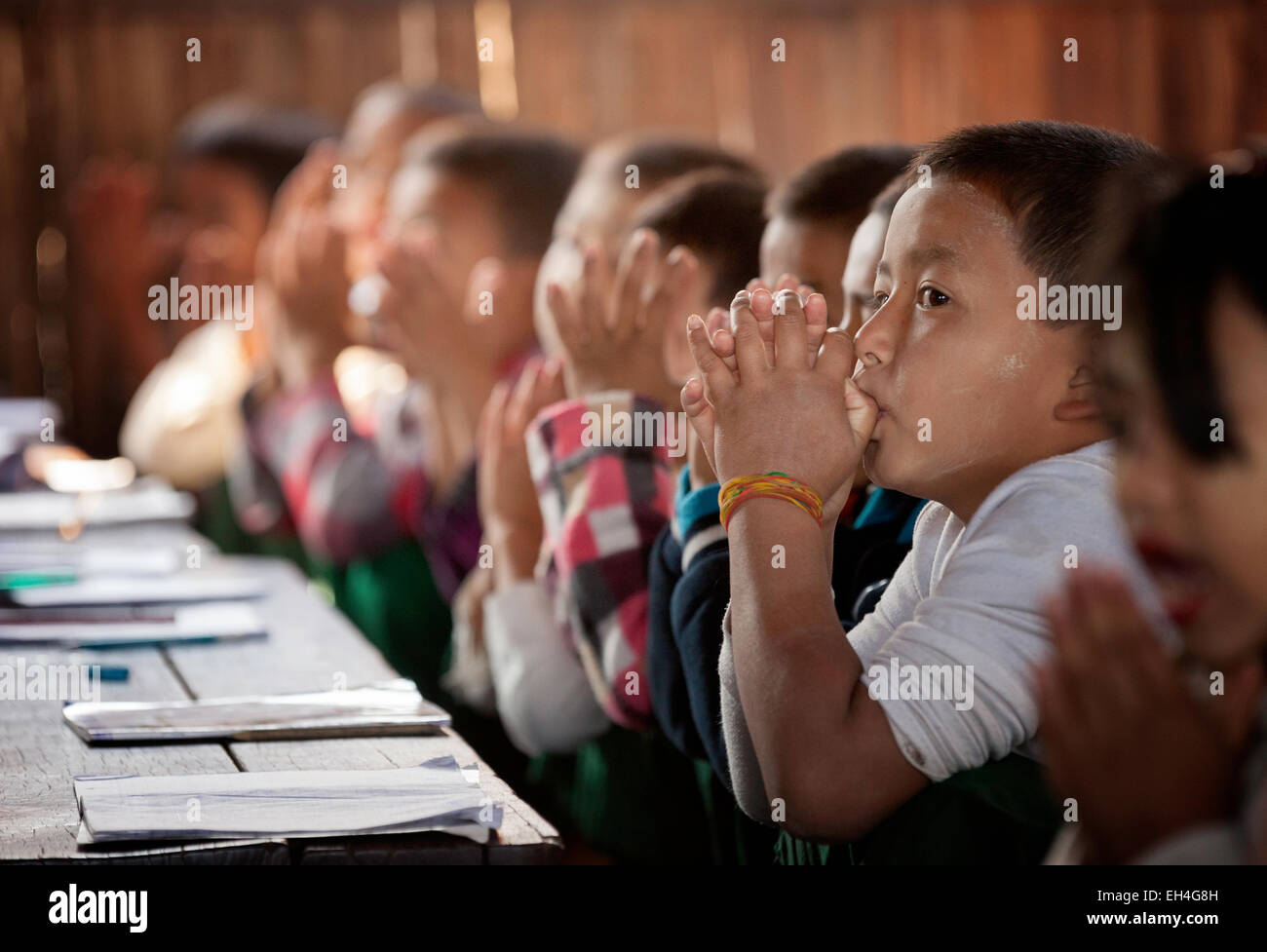 School children praying in their classroom at the start of the school day, Kar Lar village school, Inle Lake, Myanmar - Stock Image