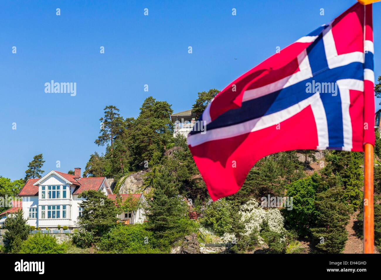 Norway, Oslo, Oslofjord, dwelling on one of the many islands Fjord with the Norwegian flag in the foreground - Stock Image