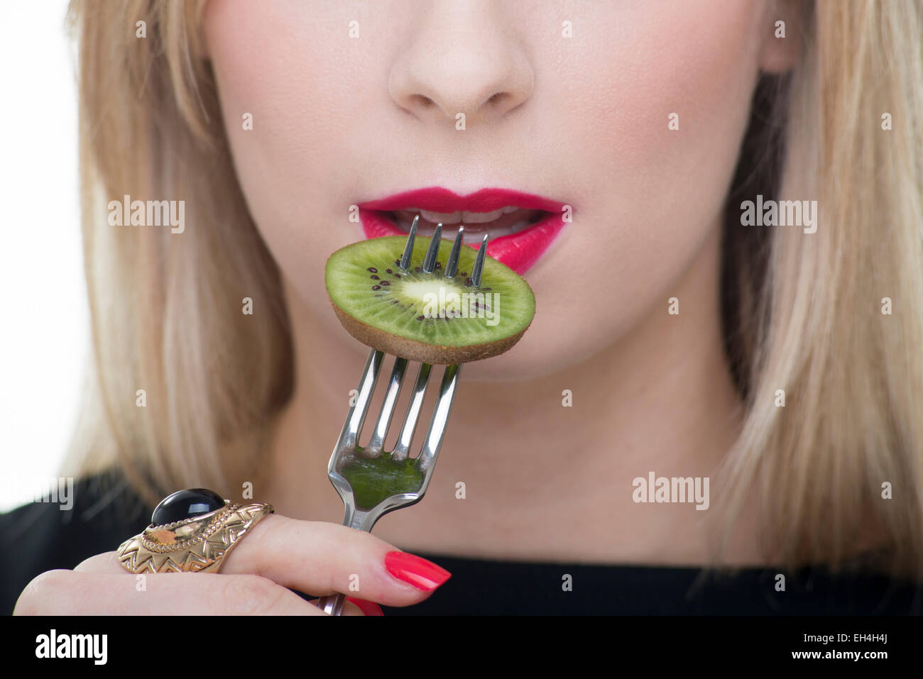 blonde woman eating a kiwi fruit with a fork - Stock Image