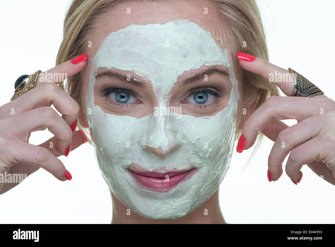 blonde woman with a face mask skincare - Stock Image