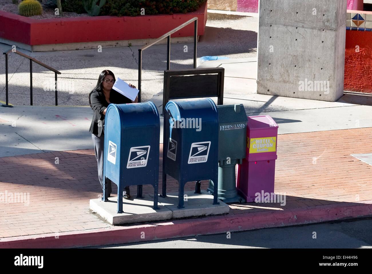 Woman mailing documents via public USPS mailbox - Stock Image