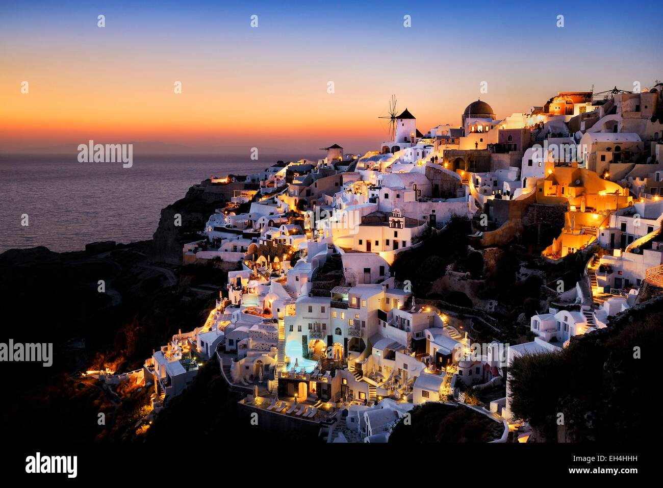 Greece, Cyclades, Santorini island (Thera, Thira), windmills and village of Oia at sunset - Stock Image
