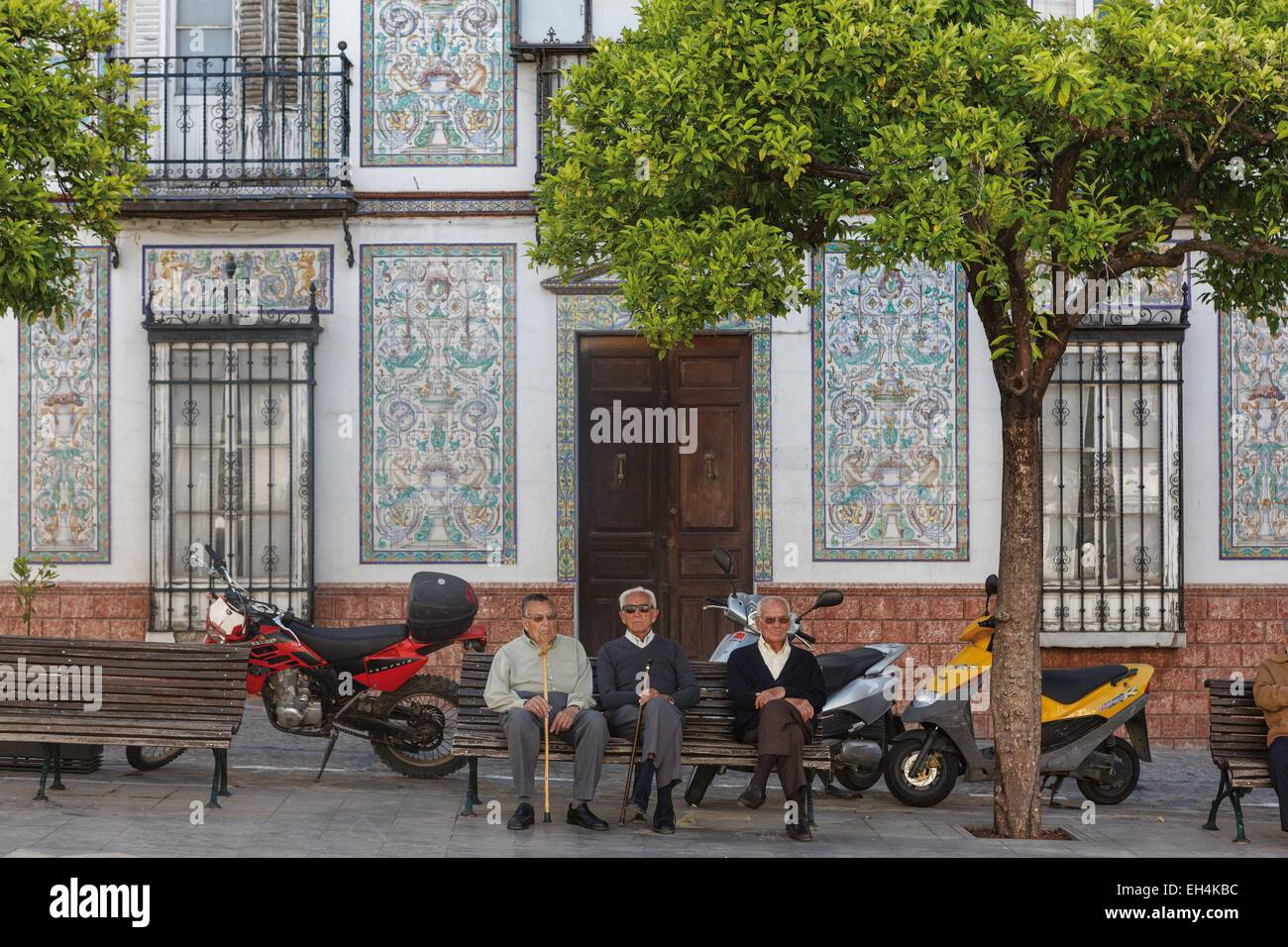 Spain, Andalusia, Cadix, Ubrique, older men sitting on a bench in the public square in front of a house decorated - Stock Image