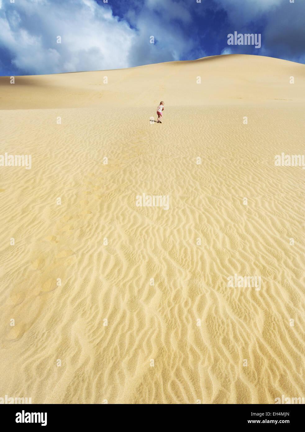 Girl running up Te Paki sand dune in New Zealand - Stock Image