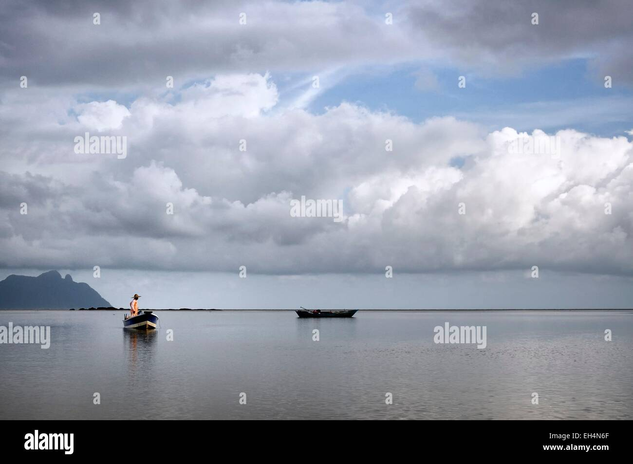 Malaysia, Borneo, Sarawak, Bako National Park, fisherman on a boat on the South China sea, cloudy sky - Stock Image