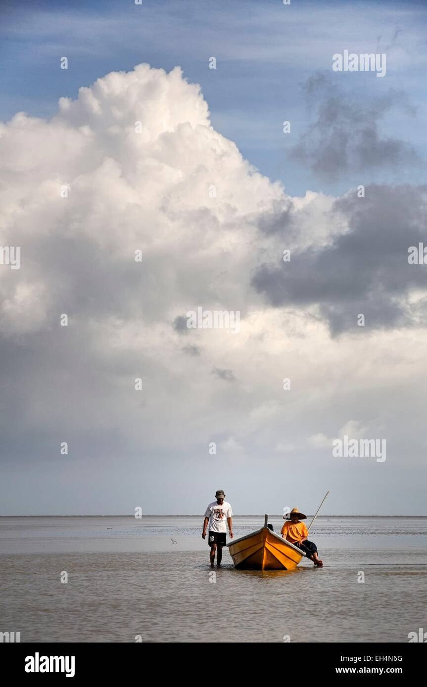 Malaysia, Borneo, Sarawak, Bako National Park, fishermen on a boat on the South China sea at low tide, cloudy sky - Stock Image