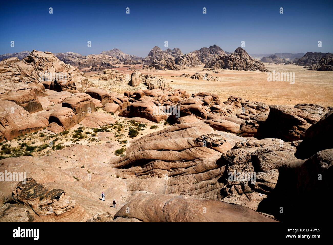 Jordan, Wadi Rum desert, protected area listed as World Heritage by UNESCO, 2 persons walking on the mount Jebel - Stock Image