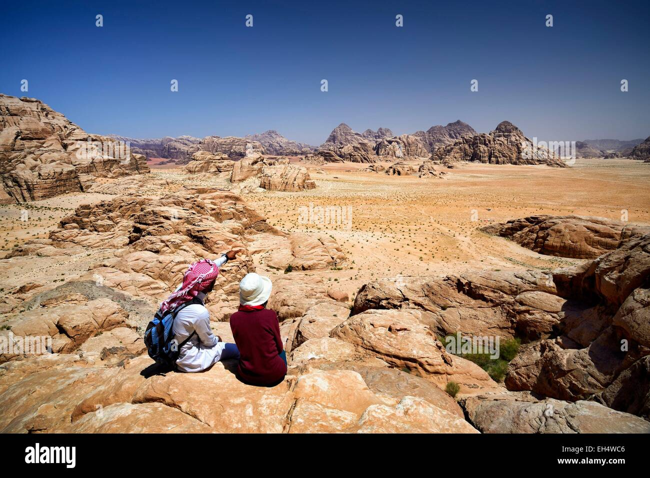 Jordan, Wadi Rum desert, protected area listed as World Heritage by UNESCO, tourist and local Bedouin guide seated - Stock Image