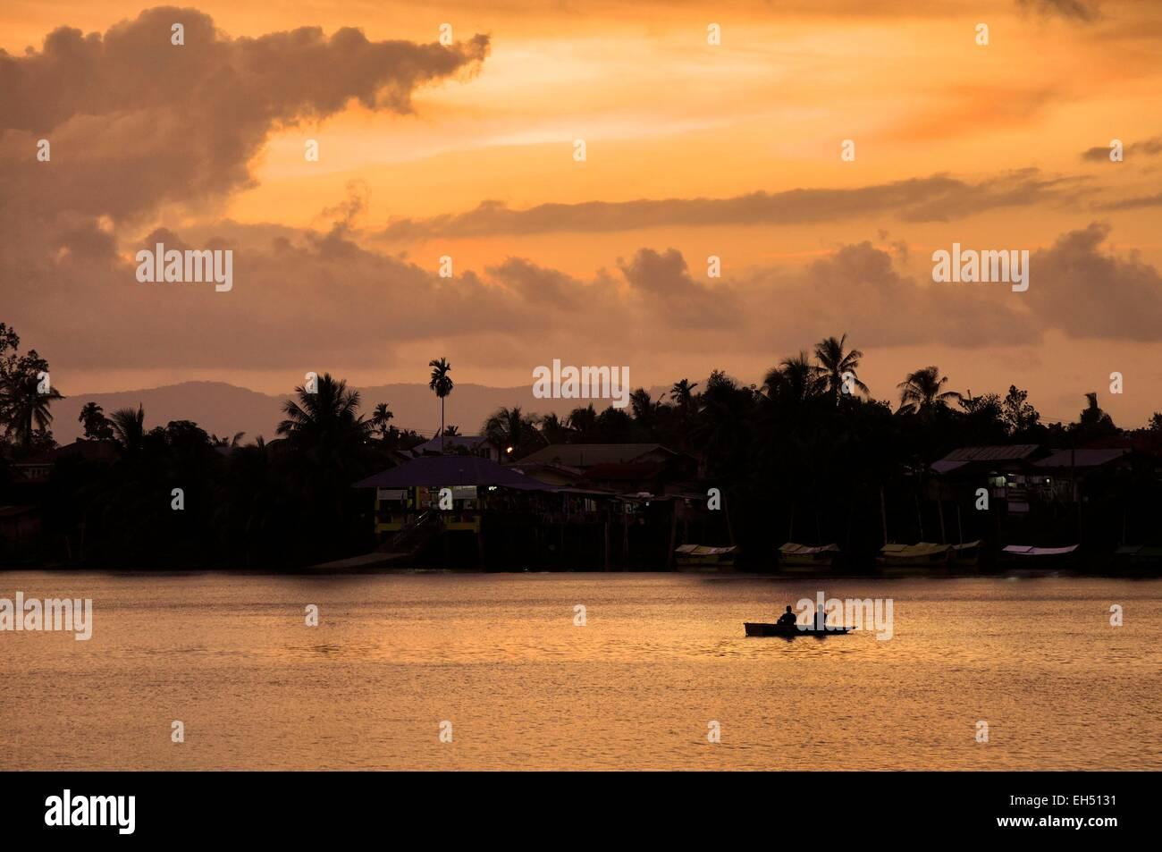 Malaysia, Borneo, Sarawak, Kuching, silhouette of fishermen on a boat on Sungai Sarawak river at sunset - Stock Image