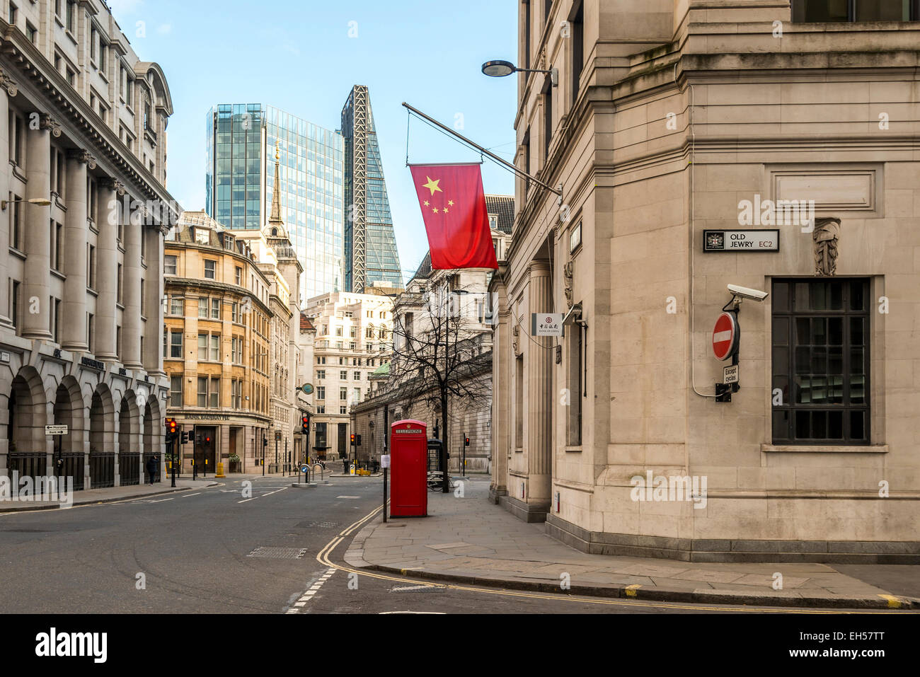 The Bank of China flies the Chinese flag outside its London branch of the bank behind which is the Cheesegrater - Stock Image