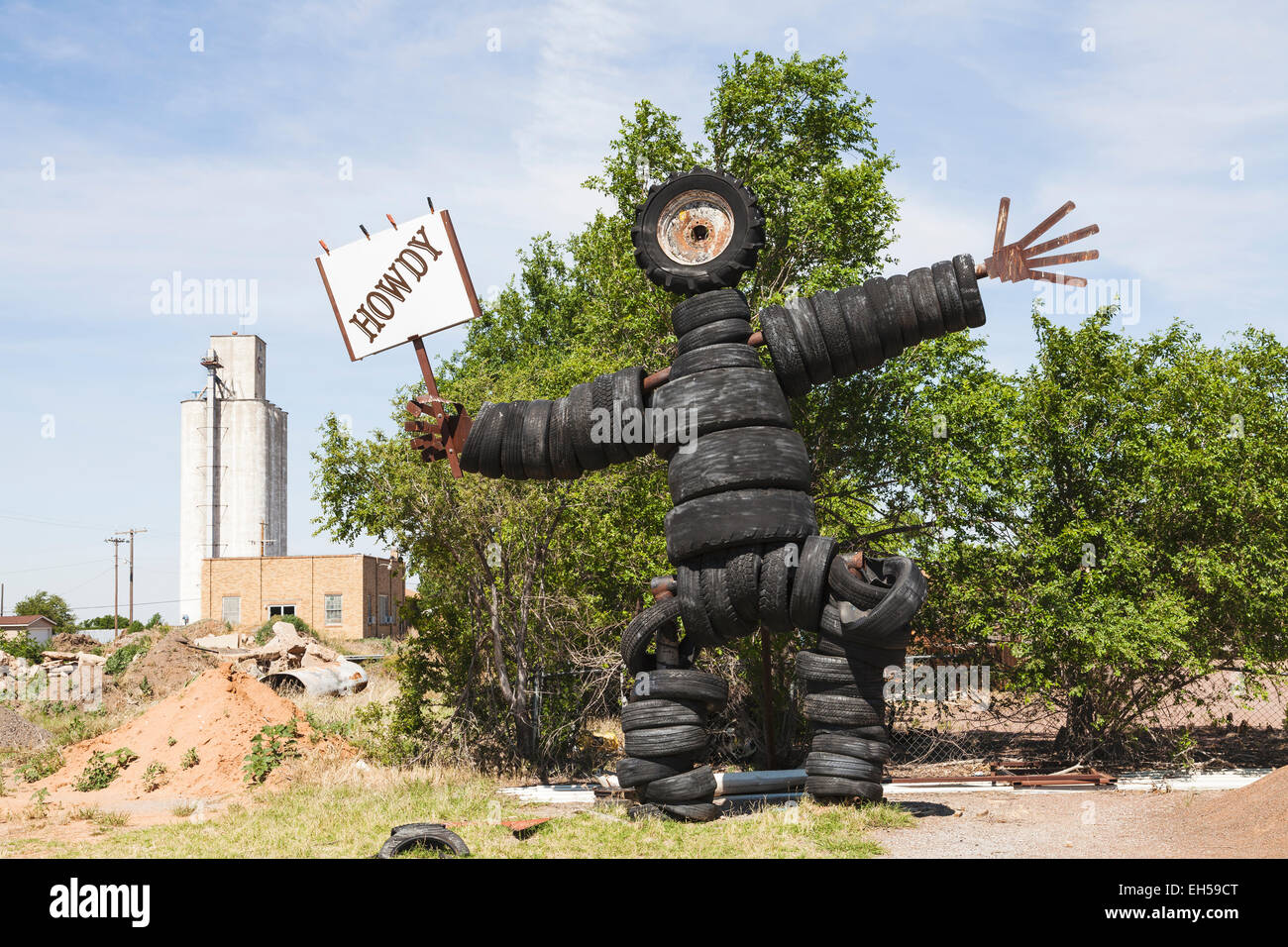 Sculpture of a man made from used automobile, truck and tractor tires in Roosevelt, Oklahoma holding a Howdy sign. Stock Photo