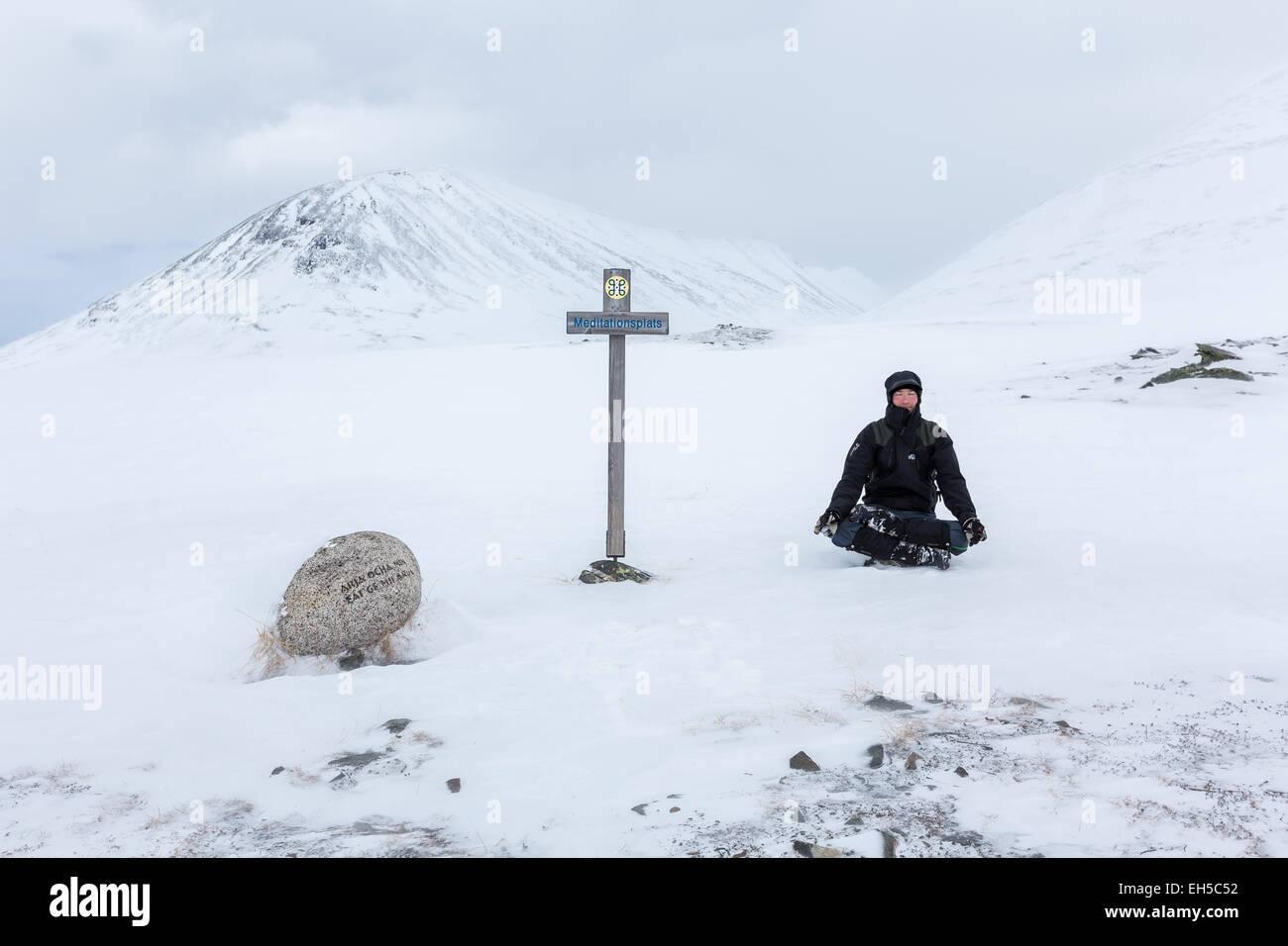 Meditating at Kungsleden trail, Kebnekaise mountain area, Kiruna, Northern Sweden, Europe, EU - Stock Image