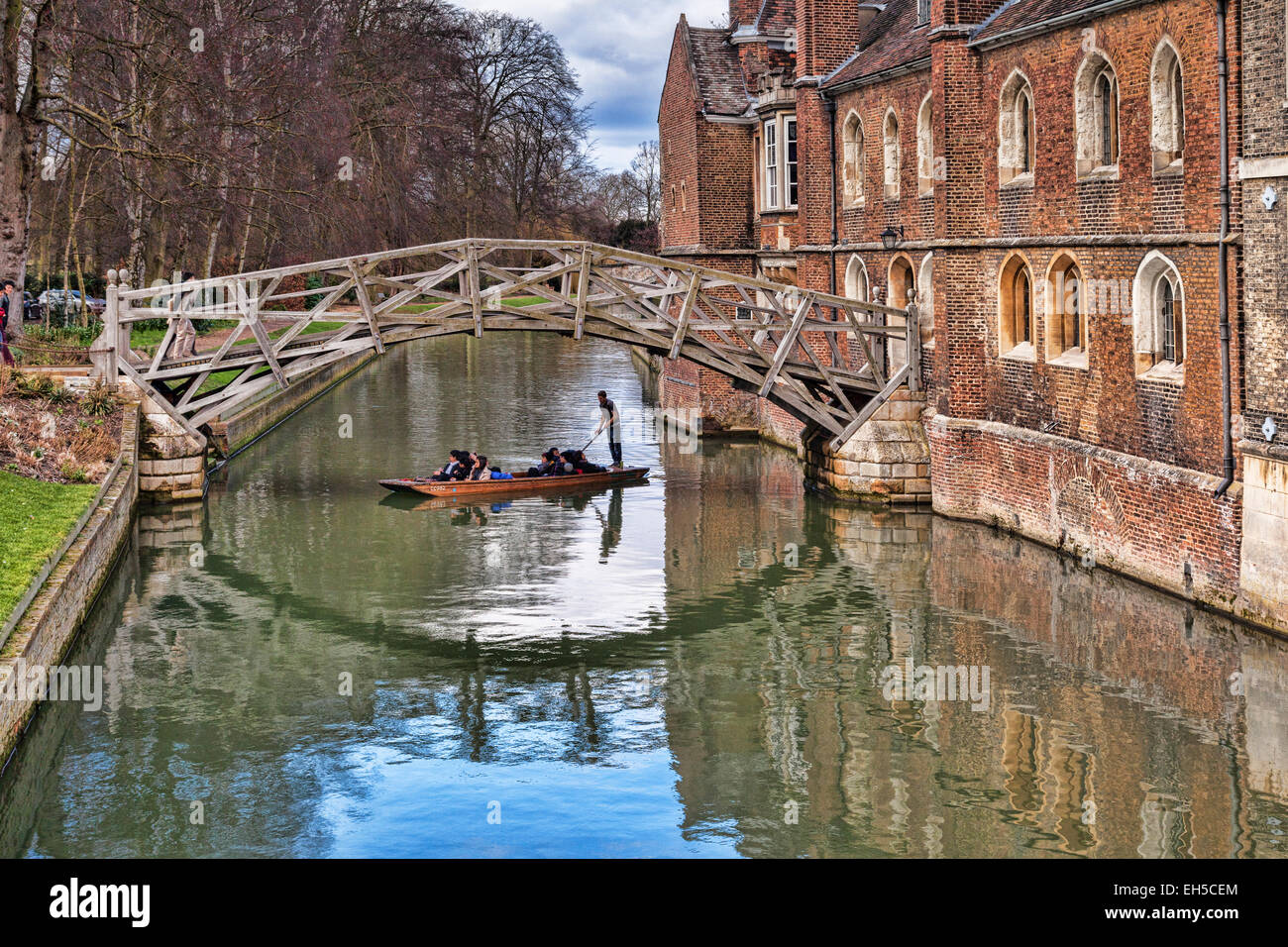 The Mathematical Bridge, Cambridge, which joins two parts of Queens College, with a punt passing underneath. - Stock Image