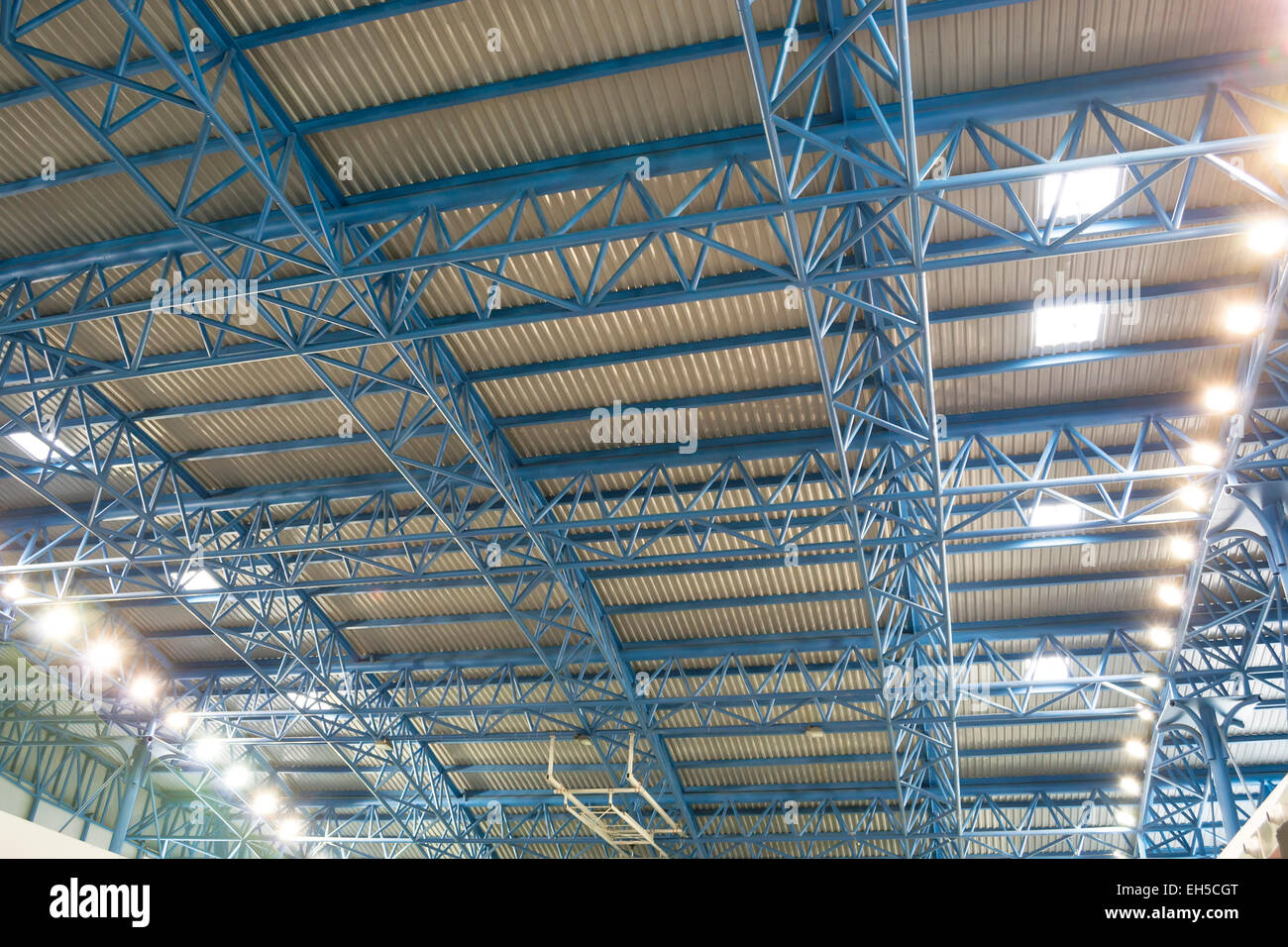 Metallic frame structure supporting a roof with artificial and natural lighting - Stock Image