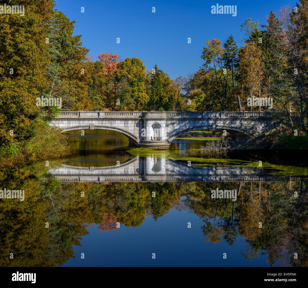 Romantic old stone bridge over a river in autumn scenery - Stock Image