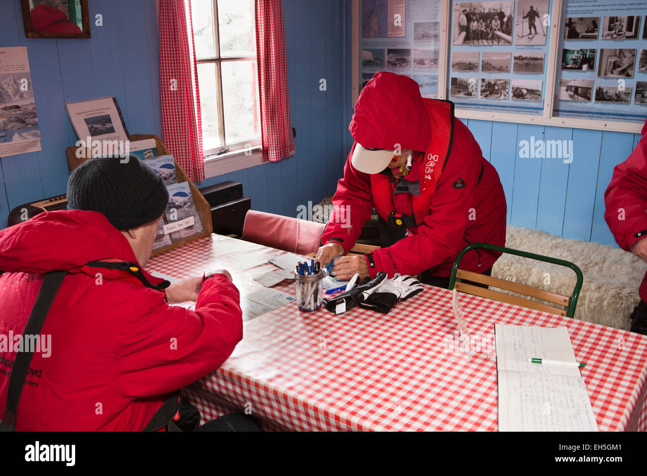 Antarctica, Port Lockroy British base museum, tourists writing postcards to post in most southerly Royal Mail post Stock Photo