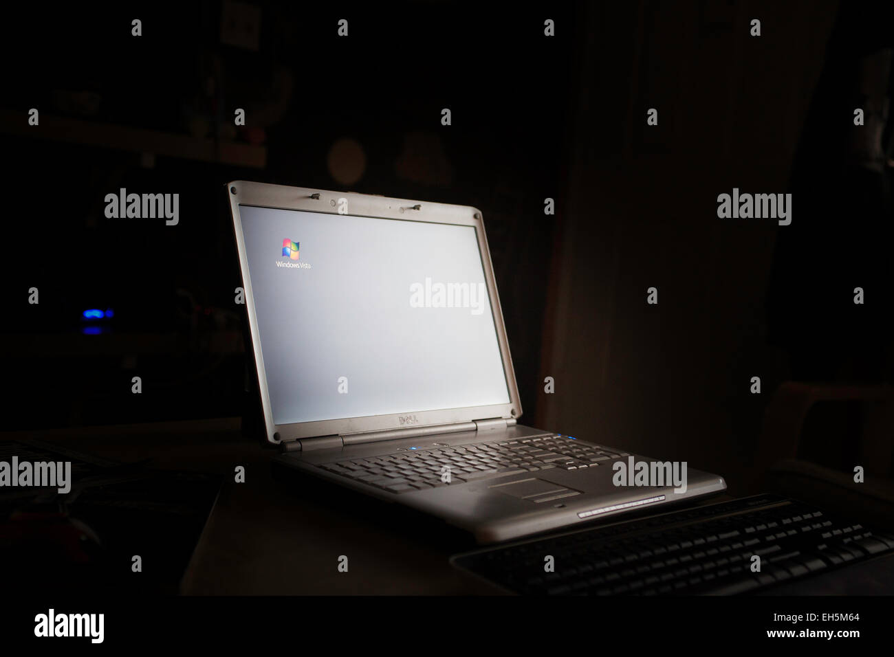 A Dell Laptop Computer in a darkened Room with Windows Vista screen saver active - Stock Image