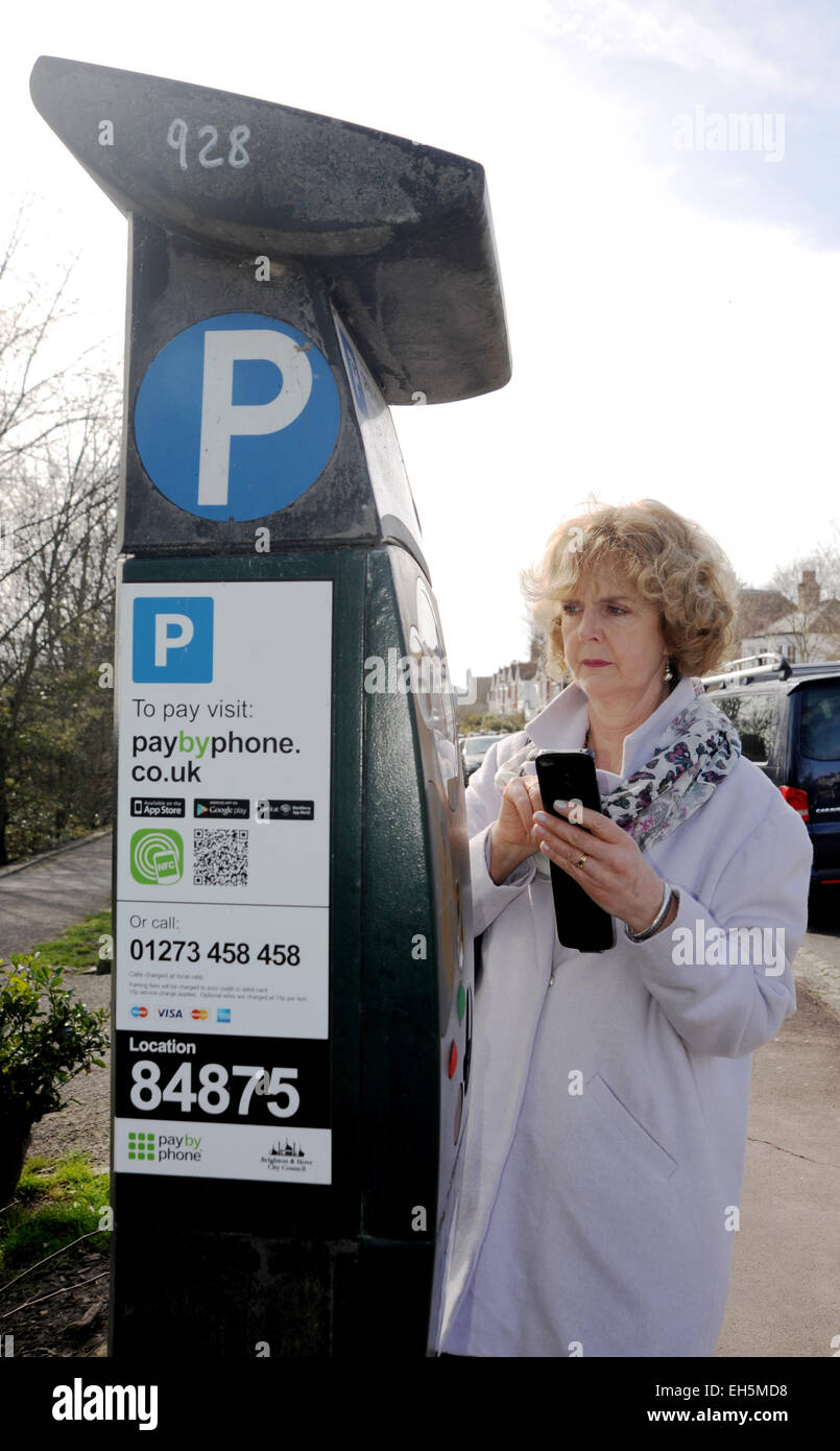 Female driver pays for parking meter using a paybyphone mobile phone app in Brighton UK - Stock Image