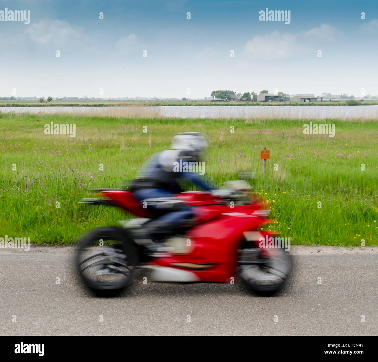 Fast motorcyclist on a red motorbike near e nature reserve of Staatsbosbeheer. - Stock Image