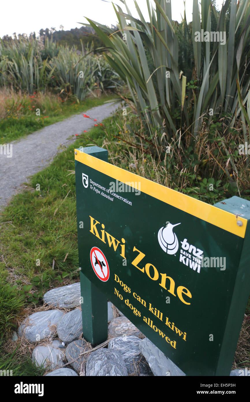 Kiwi zone conservation sign New Zealand bird trail preserve doc dog warning park - Stock Image