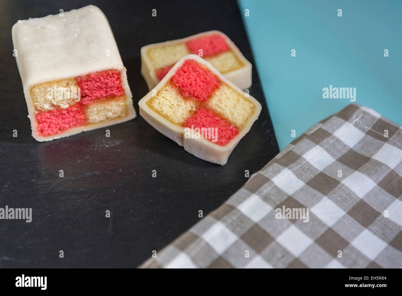 Closeup of a Battenberg cake with a brown checked napkin in the foreground - Stock Image