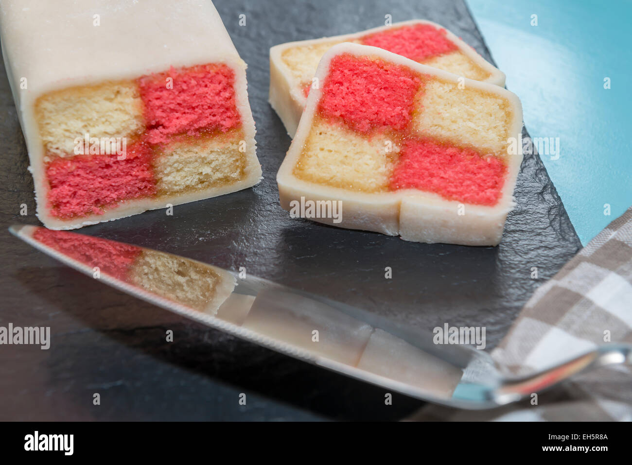 Closeup of a Battenberg cake reflected in a cake slice in the foreground - Stock Image
