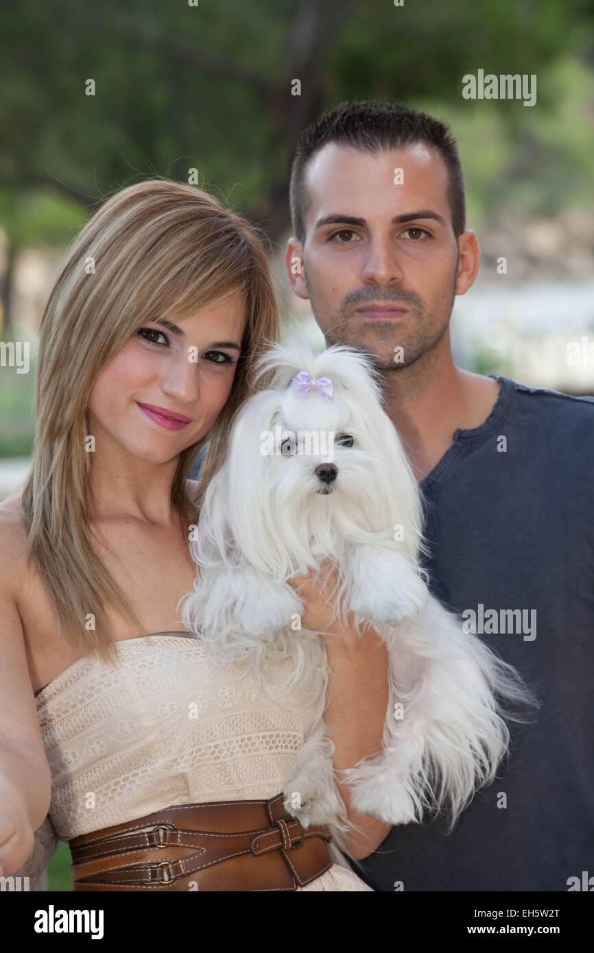 couple holding family pet dog - Stock Image