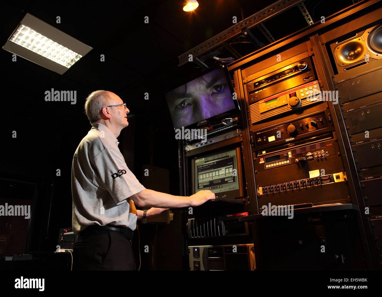 A man at the controls of a cinema projection room - Stock Image