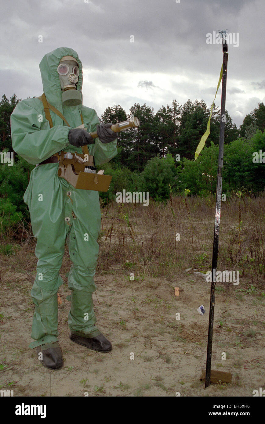 Soldier in protective suit reconnoiters chemical weapons - Stock Image