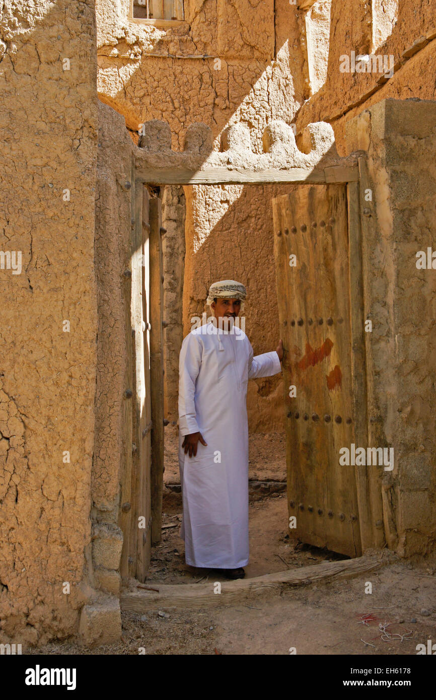 Man in doorway of old mudbrick building, Al-Hamra, Oman Stock Photo
