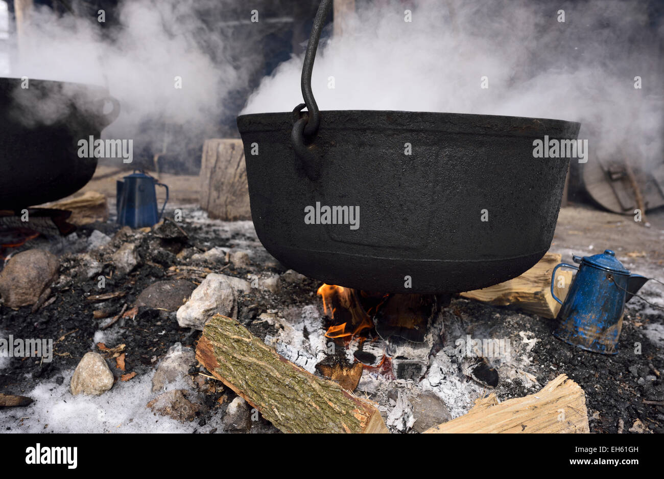 Traditional method of evaporating sap in cast iron cauldron outdoors to produce maple syrup Ontario Canada Stock Photo