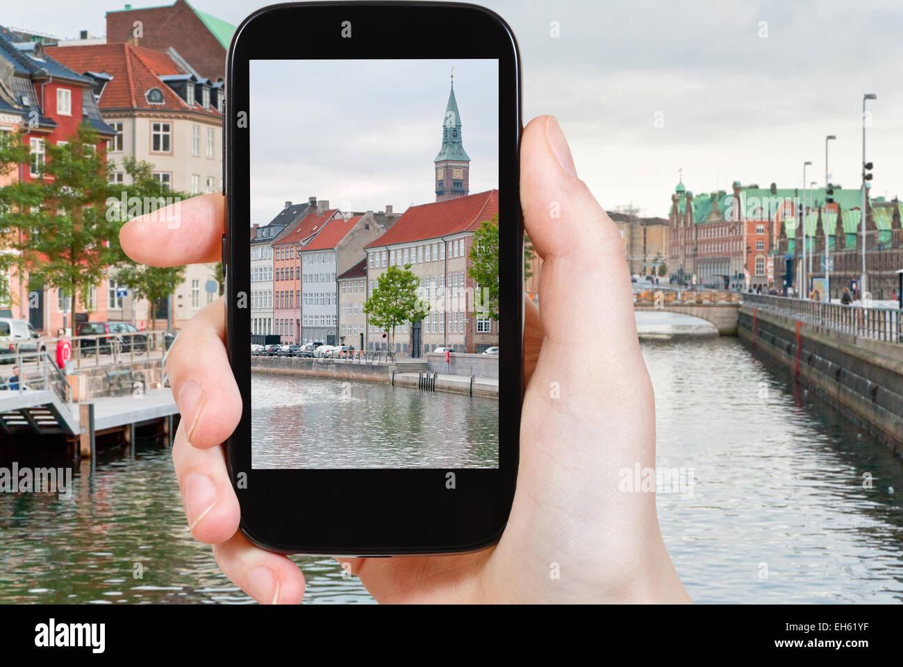 travel concept - tourist taking photo of Copenhagen cityscape on mobile gadget, Denmark - Stock Image