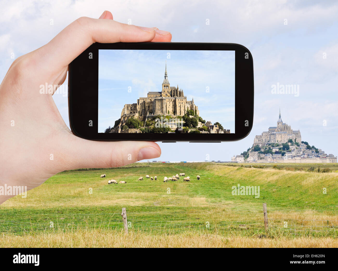travel concept - tourist take photo of mont saint-michel abbey, Normandy, France on mobile gadget - Stock Image