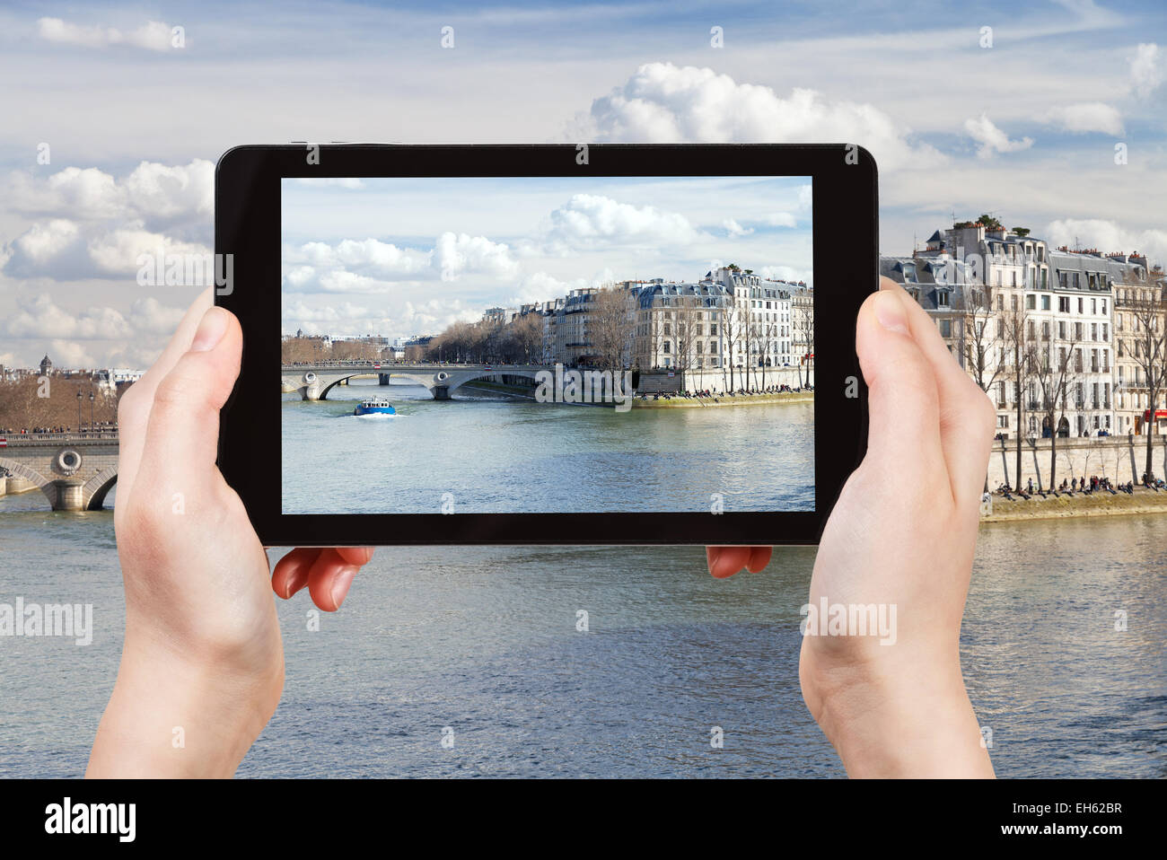 travel concept - tourist taking photo of Seine river and Pont Louis-Philippe in Paris on mobile gadget, France - Stock Image