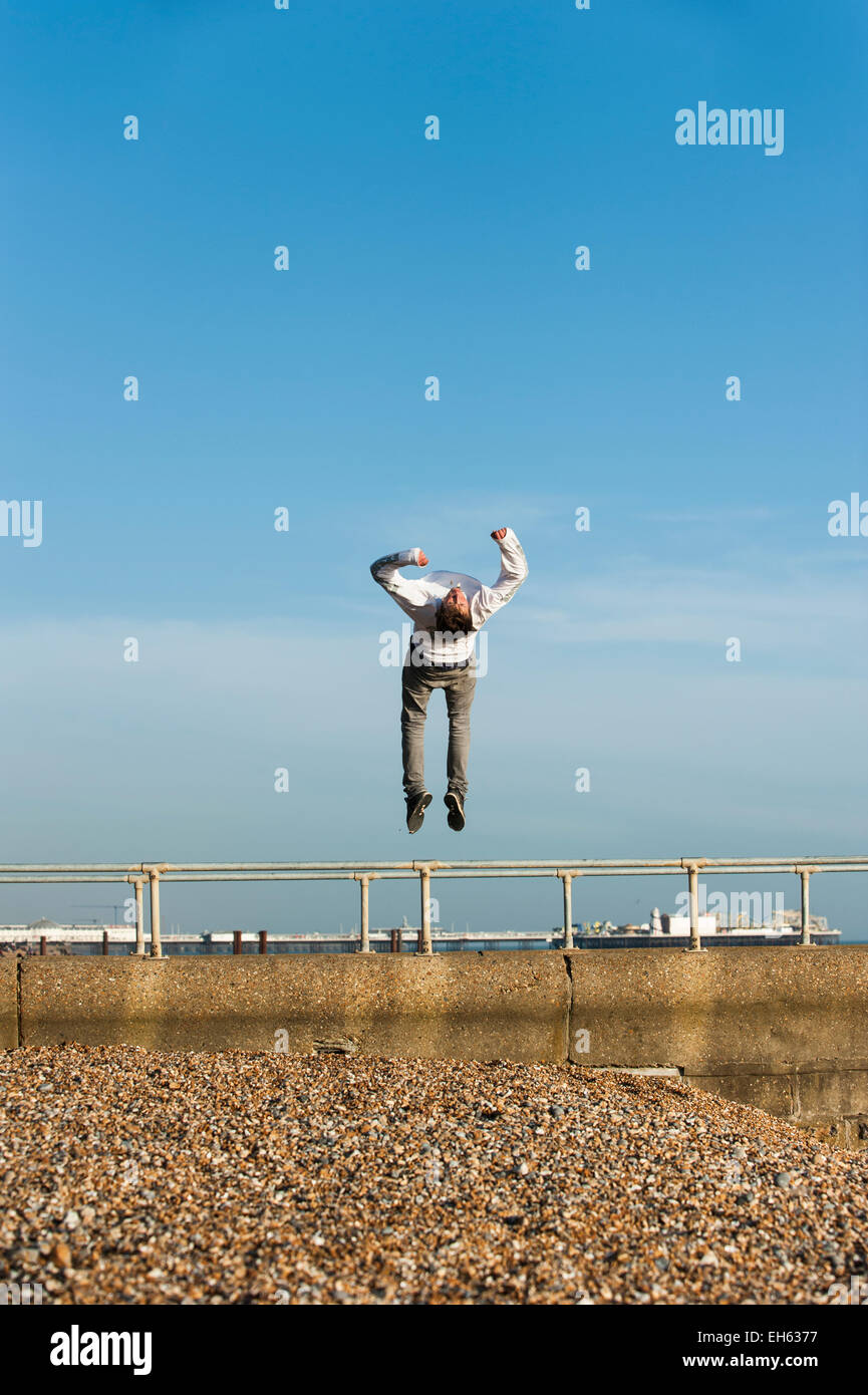 A young man does somersaults and back flips in the air whilst a group of young people are making the most of the - Stock Image