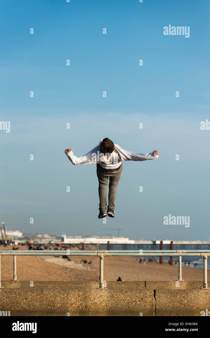 Brighton, East Sussex, UK. 7th March 2015. UK Weather: A group of young A young man does somersaults and back flips - Stock Image