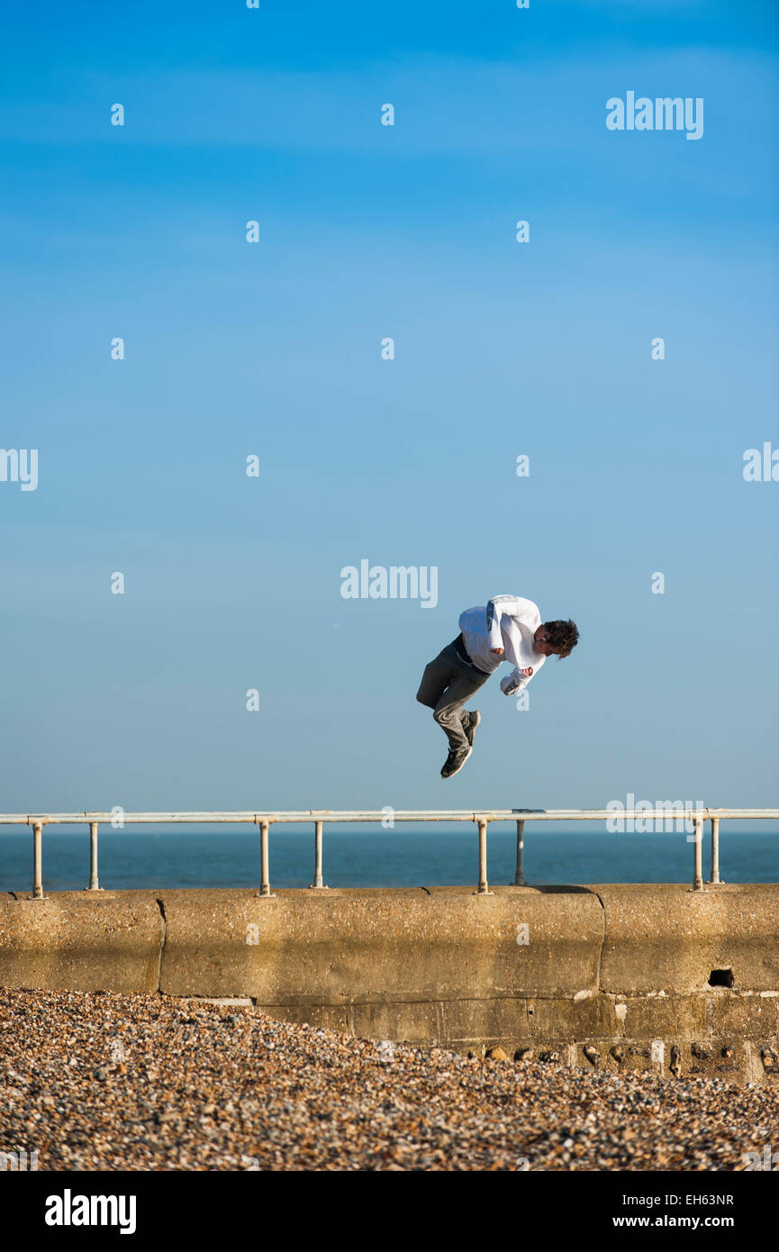 A young man twists in the air whilst a group of young people are making the most of the sunny Spring weather practicing Stock Photo
