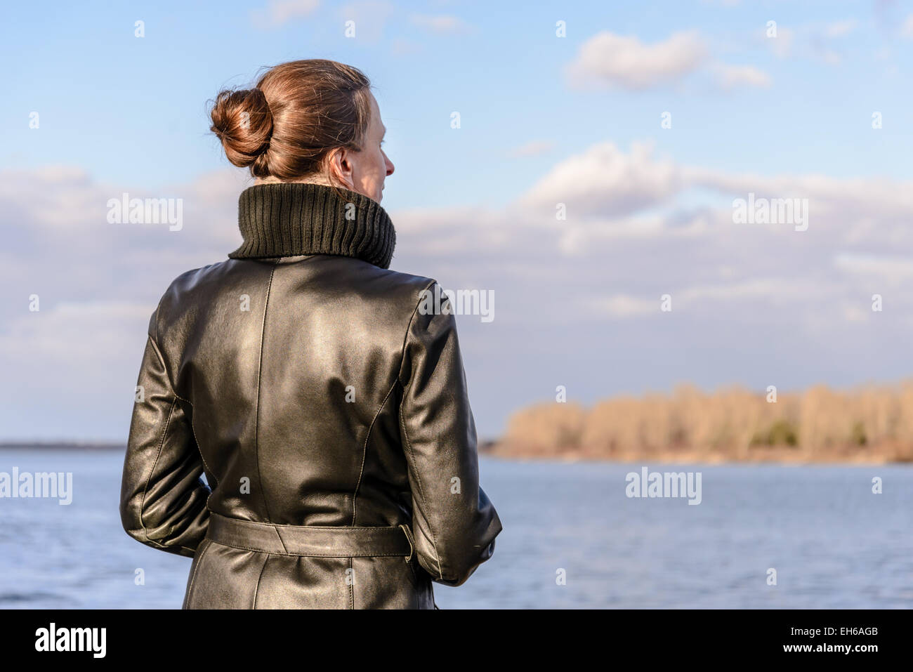 A woman with a chignon and a black leather coat is watching the landscape close to the lake or the river during - Stock Image