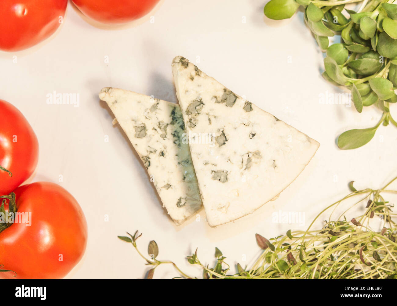 Two triangles of blue cheese, between herbs and tomatoes - Stock Image