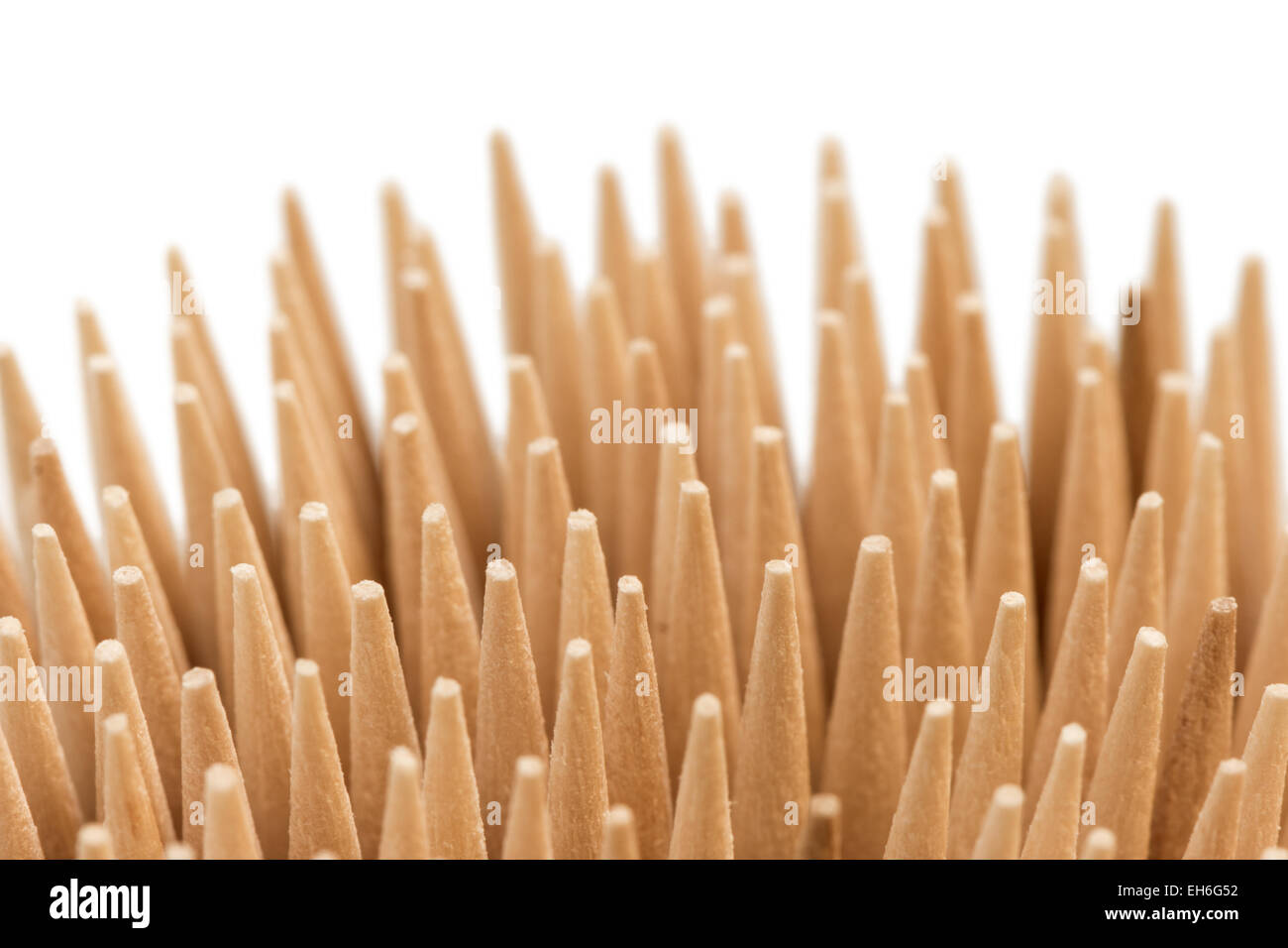 Extreme closeup of stack of wooden toothpicks or cocktail sticks, isolated on white background - Stock Image