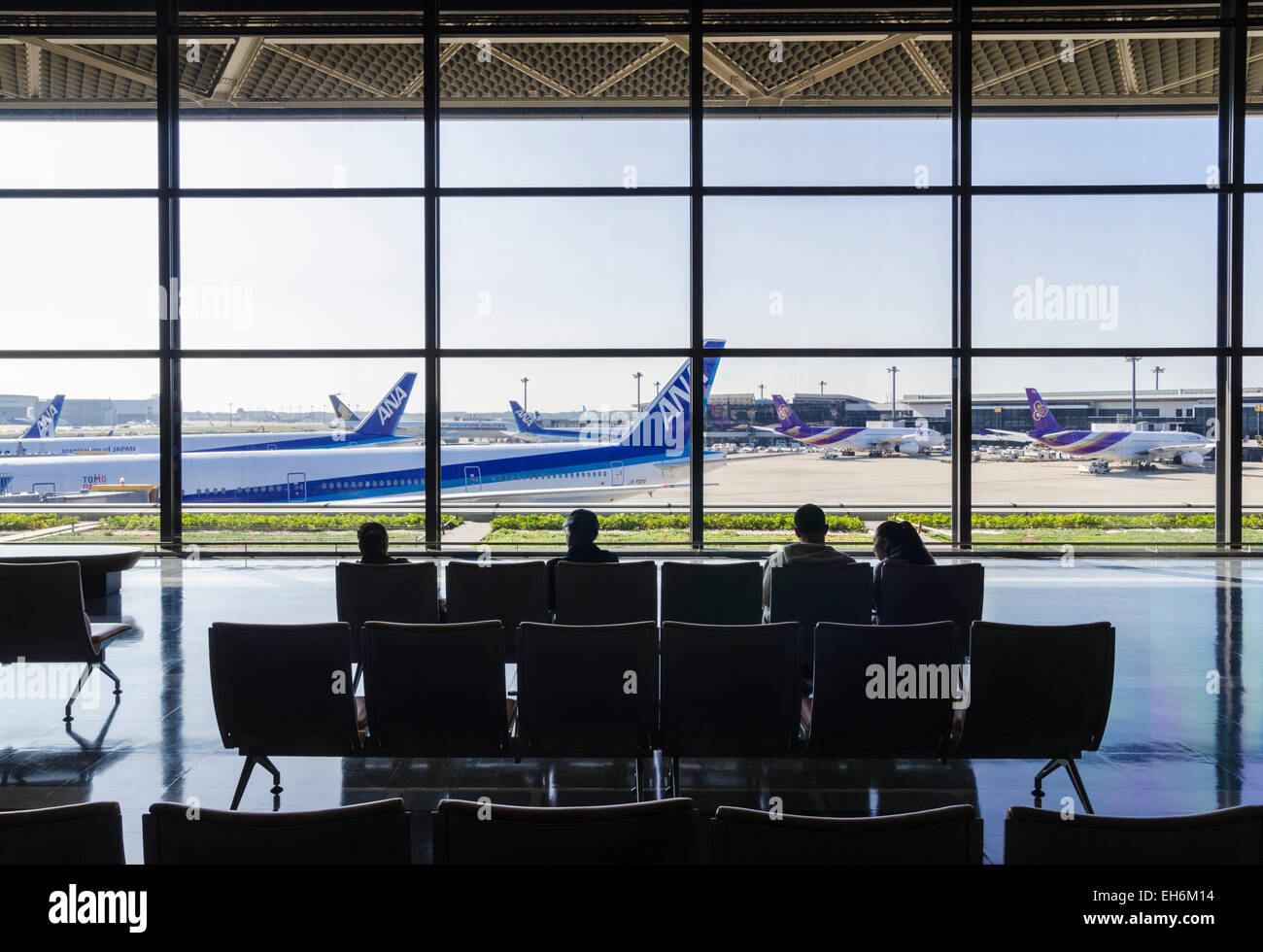 People seated in Narita Terminal 1, looking through large glass windows over the terminal gates at Narita International - Stock Image