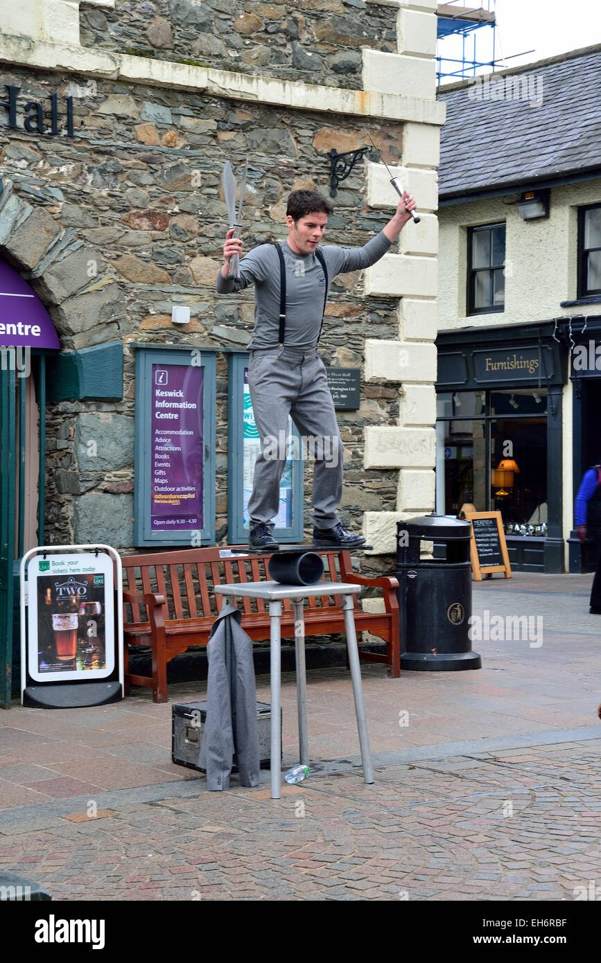 street performer in keswick west cumbria uk juggling knives and balancing on a table - Stock Image